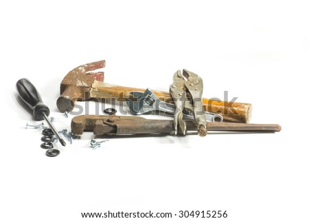 Tools with traces of rust. Hammer, adjustable wrench, pipe wrench, pliers, screwdriver and screws on a white surface.