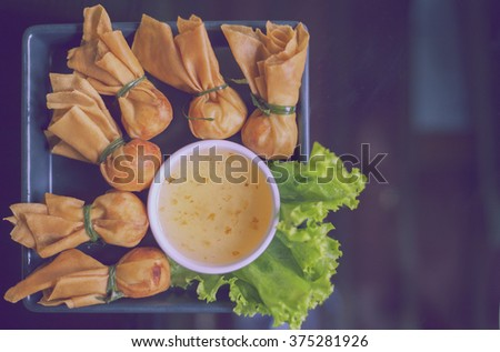 Toong thong,Thai food, oriental deep fried wontons filled with prawn and spring onion, served with dumpling and sauces,vintage color - stock photo