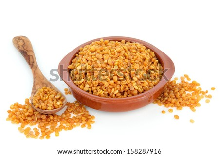 Toor dahl food ingredient in a terracotta bowl and spoon over white background.