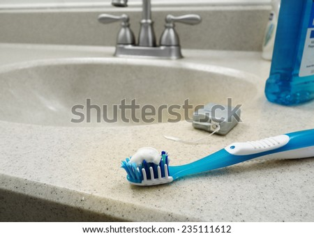 Tooth brush, dental floss and mouthwash on the bathroom sink                                - stock photo