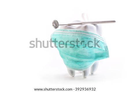Tooth with a sterile mask and mirror dentist on a white background - stock photo
