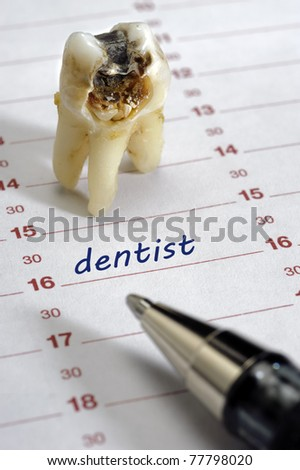 tooth with dental caries and dentist date in calendar - stock photo