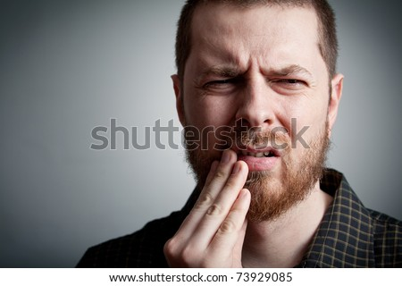 Toothache - suffering young man with teeth problems - stock photo