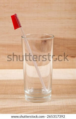 Toothbrush in a glass on a wooden board. - stock photo