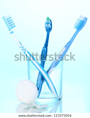 Toothbrush in glass, dental floss and chewing gum on blue background - stock photo