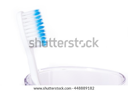 Toothbrush with blue color indicator on end of extra thin bristle's tips laying on clear glass cup against white background, selective focus - stock photo