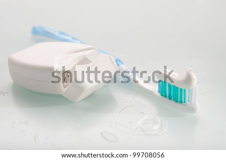 Toothbrush with toothpaste and dental floss on light background - stock photo