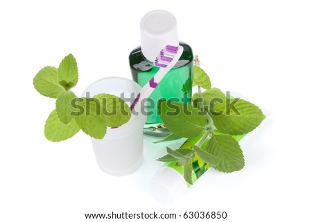 Toothbrush with toothpaste and fresh leaves of mint  on a white background. - stock photo