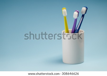 Toothbrushes in a ceramic holder - stock photo