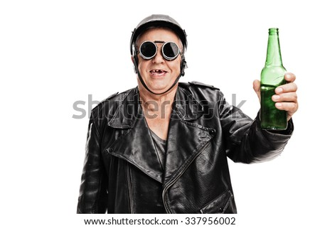Toothless senior motorcyclist in black leather jacket and goggles holding a bottle of beer and looking at the camera isolated on white background - stock photo