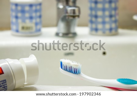 toothpaste and toothbrush in bathroom - stock photo