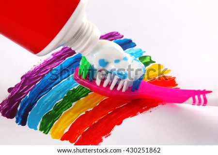 Toothpaste and toothbrush on rainbow background - stock photo