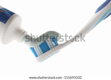 Toothpaste being squeezed onto toothbrush - stock photo