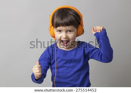 toothy smile for young preschool girl listening to music with headphones - stock photo