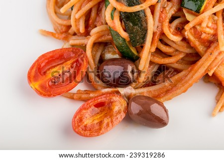 Top angle view of a plate of Italian spaghetti pasta with tomato based sauce,  olives and fresh cherry tomato. - stock photo