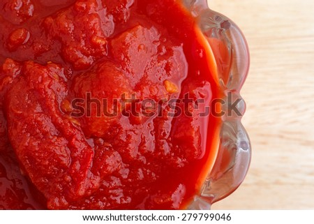 Top close view of a bowl filled with crushed tomatoes and jalapeno peppers on a wood table top. - stock photo