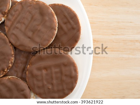 Top close view of a group of organic rice cookies with milk chocolate icing on a wood table top. - stock photo