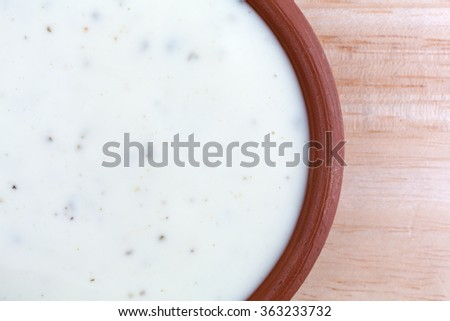 Top close view of a small bowl of ranch dressing on a wood table top illuminated with natural light. - stock photo