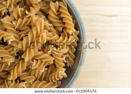 Top close view of an old stoneware bowl filled with fusilli whole wheat organic pasta on a wood table top. - stock photo