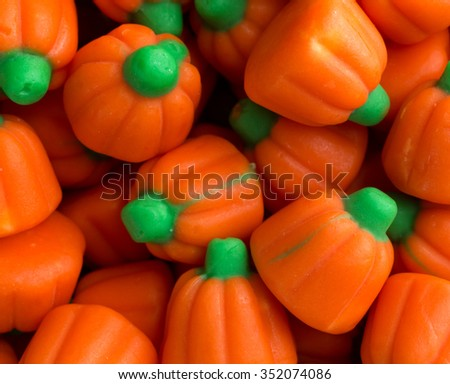 Top close view of orange and green Halloween pumpkin candy illuminated with natural light. - stock photo