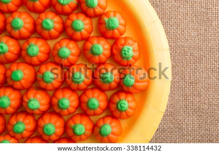 Top close view of orange and green Halloween pumpkin candy on a yellow paper plate atop a burlap tablecloth illuminated with natural light. - stock photo