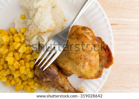 Top close view of roasted chicken, mashed potatoes and corn on a white paper plate with a fork atop a wood table top. - stock photo