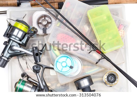 top different fishing tackles - rod, reel, line and lures in box on white background - stock photo