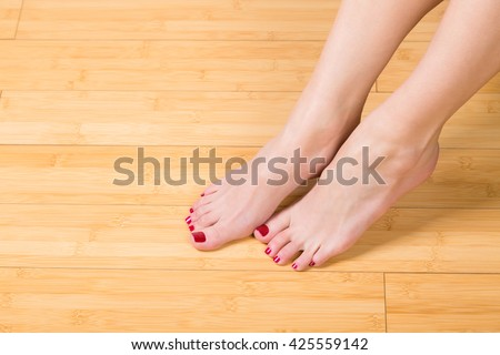 Top down close up view on neatly painted toenails and fingernails on hardwood floor