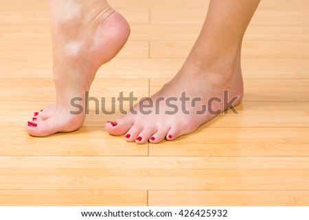 Top down close up view on neatly painted toenails and fingernails on hardwood floor - stock photo