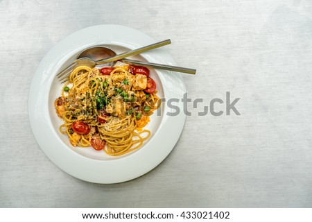Top down flat lay image of spaghetti with salmon, cherry tomatoes, green peas and shrimp fat paste topped with grated parmesan. A delicious Italian food dish with Asian touch