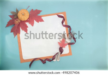 Top Down View of a Fall Table Place Setting with real maple leaves, fork and spoon, and mini pumpkin on teal background with Pale Texture Treatment and room or space for copy, text or your words.