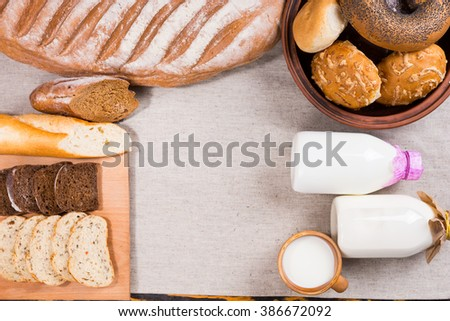 Top down view of assorted bread loaves, slices, rolls, bagels and milk, mug and bottles on cloth over wooden table with copy space - stock photo
