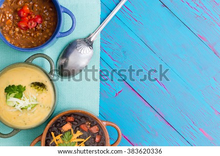 Top down view of bowls of cheese soup and chili with beans next to metal spoon on napkin over blue wooden table - stock photo