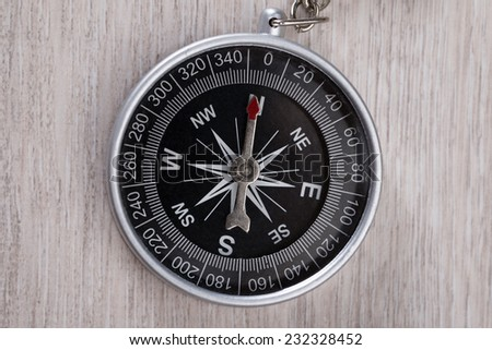 Top down view of compass on wooden table - stock photo