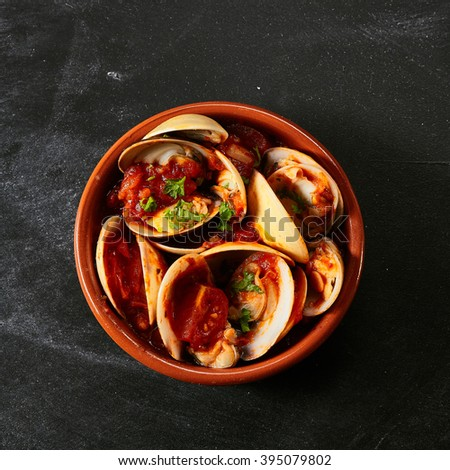 Top down view of single round red bowl of venus shells and delicious sauce as a Spanish style appetizer - stock photo
