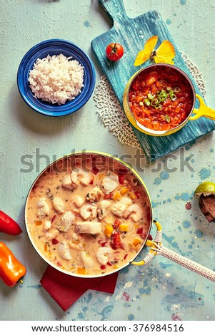Top down view of tasty Brazilian cuisine of shellfish, rice, tomato and other ingredients in pot and bowls on colorful table - stock photo