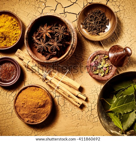 Top down view on pots of assorted whole leaf and ground herbs and spices used as Indian food cooking ingredients over cracked painted brown surface - stock photo