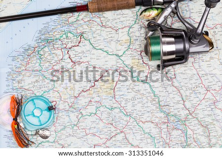 top fishing tackles - rod, reel, line and lure on norway map background. Prepare fishing  route and to journey - stock photo