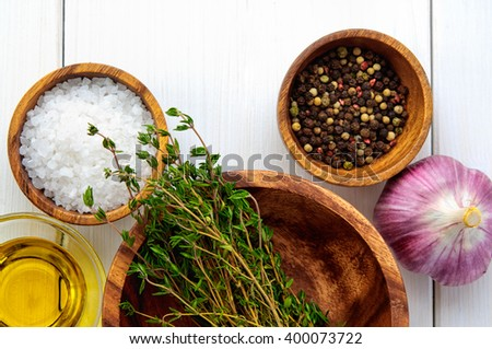 Top flat view of ingredients: salt, pepper, chili,  thyme, garlic, olive oil in bowls on white rustic wooden table. Cooking concept - stock photo