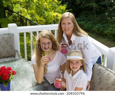 Top front view of happy mother and daughters, looking forward, drinking grapefruit juice while outdoors on patio with woods in background