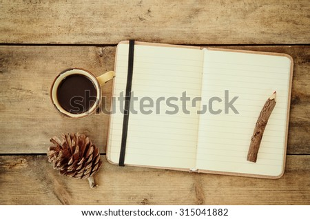 top image of open notebook with blank pages, next to pine cones and cup of coffee over wooden table. top image,