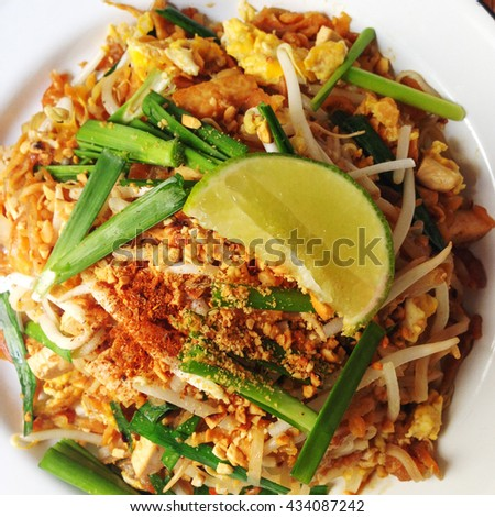 Top look of a dish of healthy authentic Padthai (an original Thai style stir fried noodle with mixed herb, spice and tamarind sauce) with grilled Tofu, mixed crushed grilled peanut and lemon wage. - stock photo