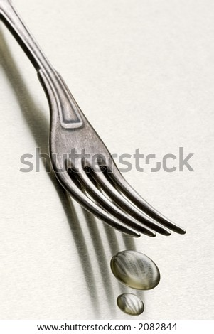 top of a fork on white with few drops under prongs
