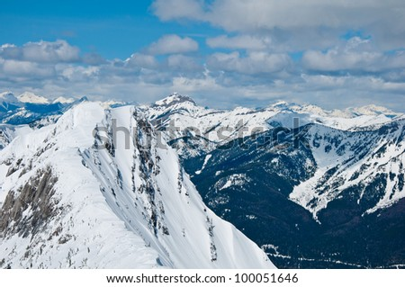 Top of a mountain view of surrounding snow covered mountains on a sunny day - stock photo