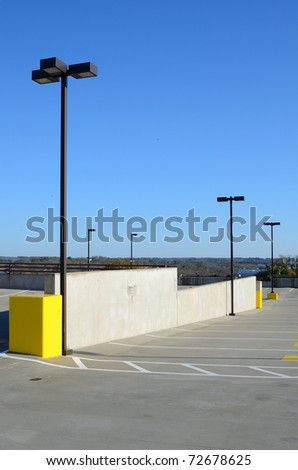 Top of a parking deck with spaces and light poles. - stock photo