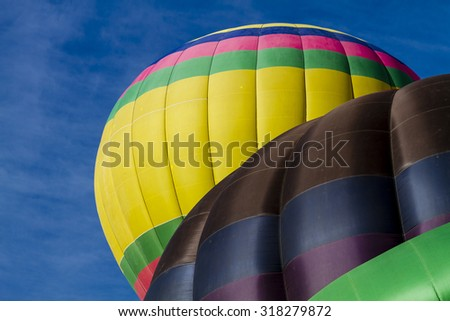 Top of brightly colored hot air balloons against blue morning sky just after take off - stock photo