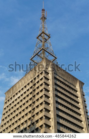 Top of old building with communication tower against blue sky