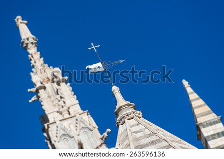 Top of Siena Cathedral's bell tower and face, white marble on a blue sky - stock photo