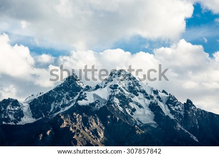 Top of snowy rock mountain on cloudy background - stock photo