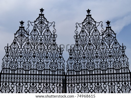 Top of the front gate to India's Presidential Palace against blue skies. - stock photo